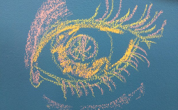an intricate drawing of an eye done in yellow and pink chalk on a blue chalkboard background.