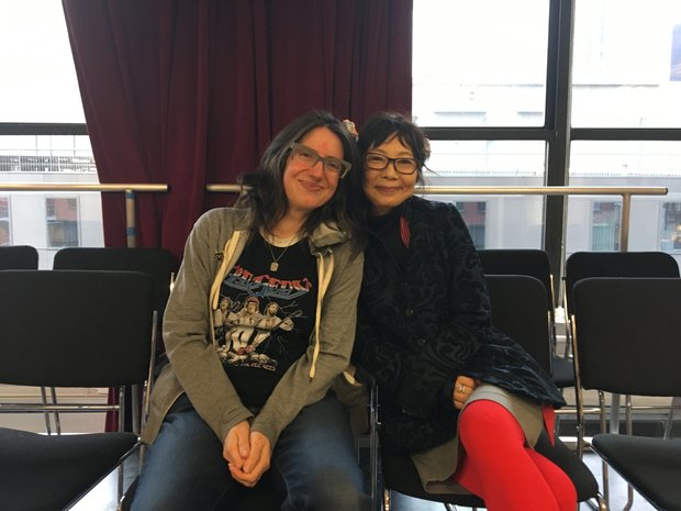 Crystal Skillman and Chiori Miyagawa sit on chairs in The Lark's BareBones Studio, leaning into each other. A red curtain partially obscures the windows behind them.