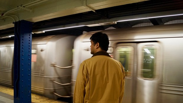 Christopher Reyes, his back to the camera, stands on a subway platform as a train pulls in.