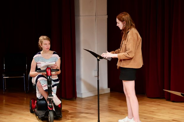Madison Ferris sits in her wheelchair and rehearses a scene with Chloe Bell, who stands next to her at a music stand. each holds a script and they face each other in a rehearsal studio with wood flooring and red curtain.