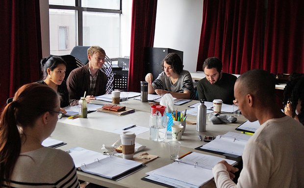 Six artists seated around a folding table, coffee cups, scripts, and other supplies in front of them. They laugh and smile at one another as they read through a play.
