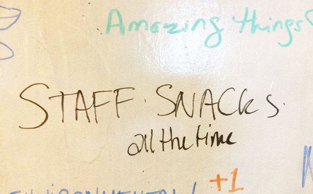"dry erase board reads ""Staff Snacks all the time"" and ""amazing things"""