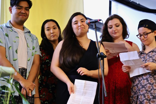 Christopher Reyes, Mona Moriya, Sarah Machiko Haber, Chloe Knight, and A.A. Brenner stand in in front of a yellow wall. There is a microphone set up in front of Sarah, who stand center, and she is holding a sheet of paper with a speech written on it.