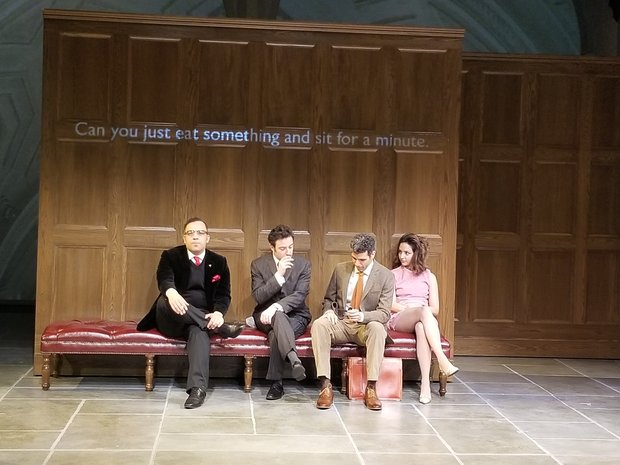 "Four actors sit on a red leather bench on a stage set with a backdrop of a tall wood paneled wall. A projection reads ""Can we just eat something and have a moment?"""