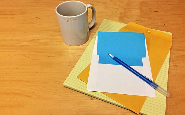 A legal pad, envelope, pen, and coffee mug rest on a wood surface.