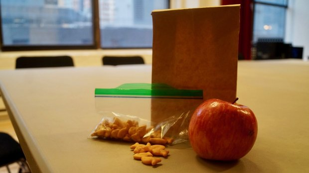 A brown paper lunch bag sitting on a table. Goldfish crackers and an apple sit in front of it.