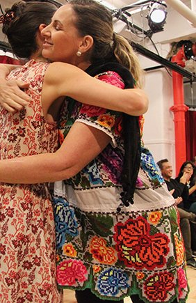 Andrea Thome and Aida Varas hug, audience members can be seen clapping behind them.