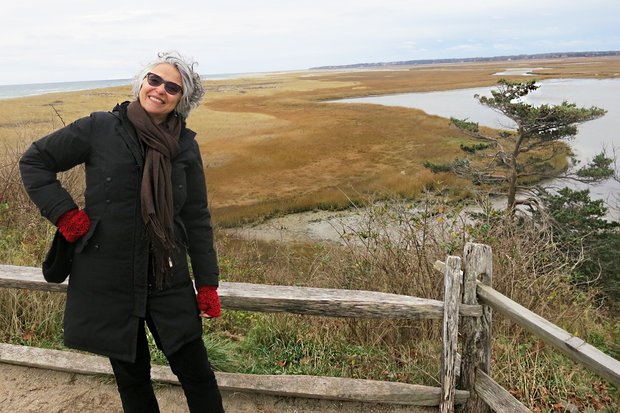 Roberta Levitow stands to the left of the frame wearing a black jacket, sunglasses, and bright red fingerless gloves. Behind her, a section of wooden fence, beyond which lies a gray river running through a yellowing field.