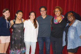 From left to right, Sasha Sharova, Alex Gonzalez, Zoe Rhulen, Rajiv Joseph, Kimille Howard, and Nissy Aya stand in front of a red curtain, their arms around each other's shoulders, smiling into the camera.