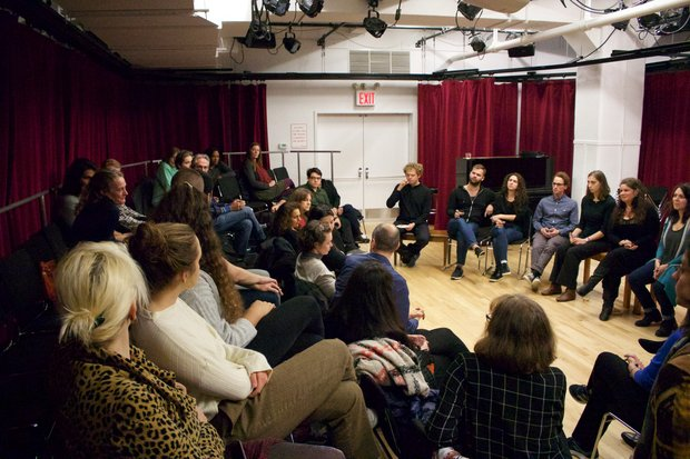 A group of panelists sit in front of a red curtain in The Lark's BareBones studio, engaged in a discussion with the audience members, who sit in three rows of chairs across from the panelists.