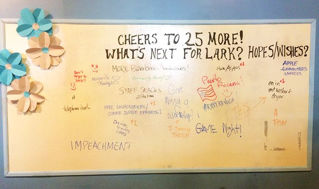 "A dry erase board decorated with paper flowers. Written across the top is ""Cheers to 25 more! What's next for Lark?"" with many short statements written in various colored marker underneath."