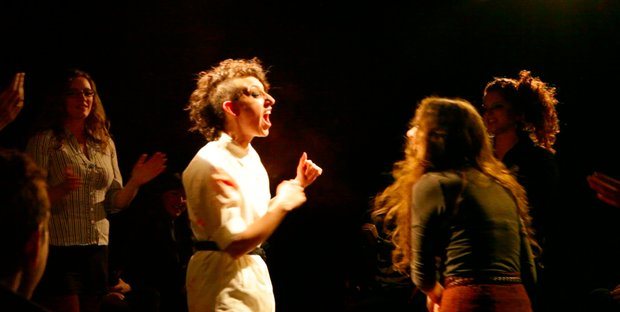 A woman, half her head shaved, stands in a white robe at the center of a stage, yelling, her fists clenched, while other women look on.