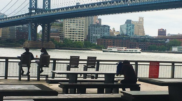 Two people with masks on have a conversation as they sit on benches overlooking the Manhattan Bridge