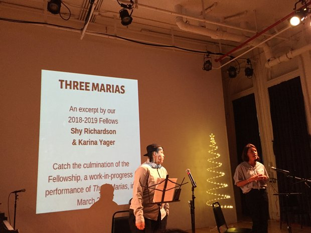 "Shy Richardson and Karina Yager speak into microphones while standing in front of a white wall on which is projected ""Three Marias, an excerpt by our 2018-2019 Fellows"""