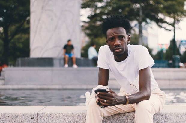 Donja R. Love sits on the edge of a fountain, looking into the camera, unsmiling, and holding his phone in his hands.