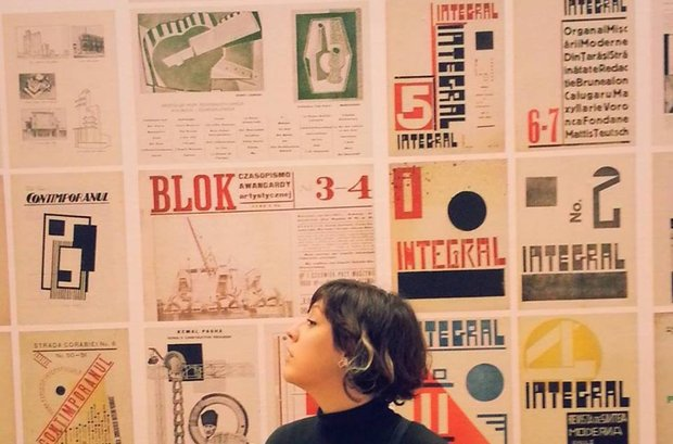 "Diana Damian Martin looks up at a wall covered in posters that feature art deco illustrastions, and many display the word ""integral"""