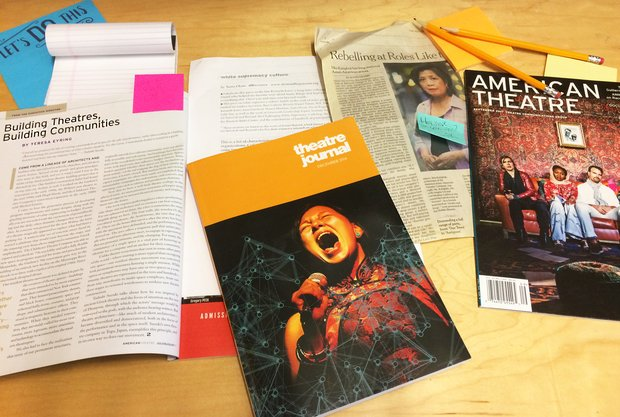 "A stack of theater magazines and printed articles with post it notes marking specific pages sits on a wood surface. The most prominent is a book titled ""theatre journal"" and the cover features a woman singing into a microphone."