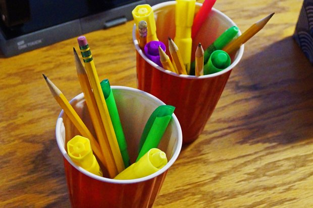 Two red cups, sitting diagonally from one another and filling most of the frame, are filled with markers, colored pencils, and highlighters.