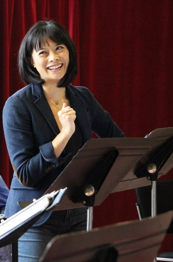 Tiffany Villarin stands at a music stand in front of a red curtain, and smile