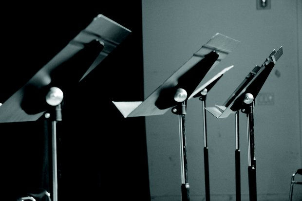 Black and white image of three empty, metal music stands in a row.