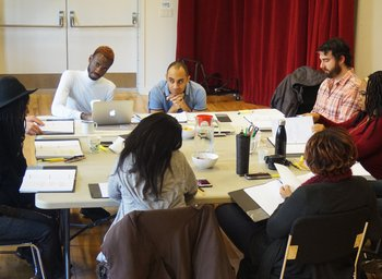 Playwright Donja R. Love and Director Saheem Ali sit at a fold out table with the cast of IN THE MIDDLE as they read through their scripts.