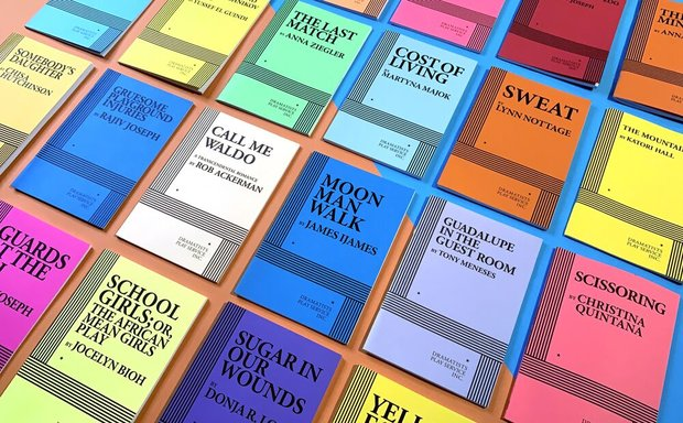 Rows of colorful acting editions of published scripts, lined up neatly across a wood surface.